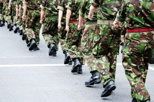 uniformed army soldiers form a straight line marching